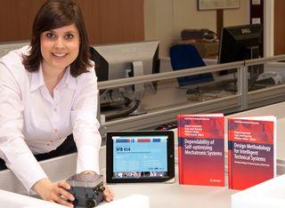 Mareen Vaßholz, Geschäftsführerin des SFB 614, mit einem Miniaturroboter, der als Demonstrator für die Ergebnisse der Forschungsarbeiten sowie der Abschlusspublikationen dient. Foto: Universität Paderborn, Heinz Nixdorf Institut